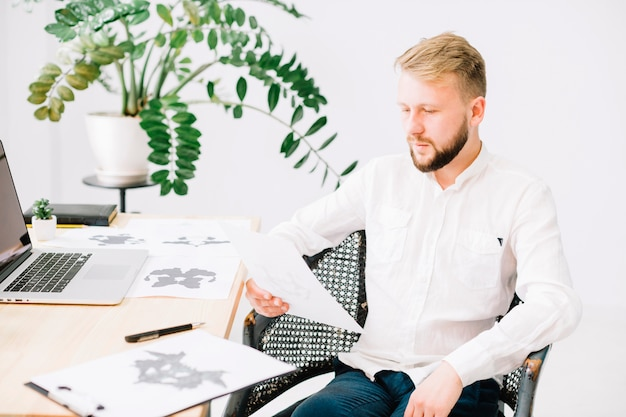 Ritratto di un giovane psicologo guardando la carta di prova inkblot rorschach in ufficio