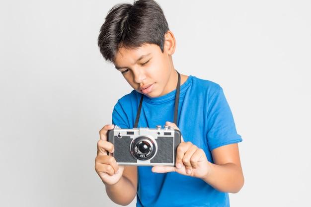 Ritratto di un giovane ragazzo con fotocamera isolata on white