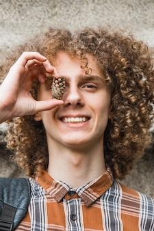 Ritratto di un giovane ragazzo dai capelli ricci in un parco estivo