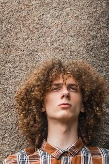 Ritratto di un giovane ragazzo dai capelli ricci tra le pietre