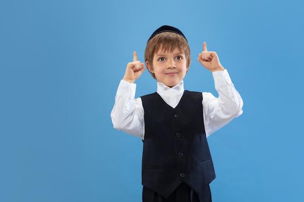 Ritratto di un giovane ragazzo ebreo ortodosso isolato su studio blu