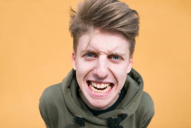 Ritratto di un giovane ragazzo malizioso vicino contro un muro arancione. un giovane arrabbiato e divertente.