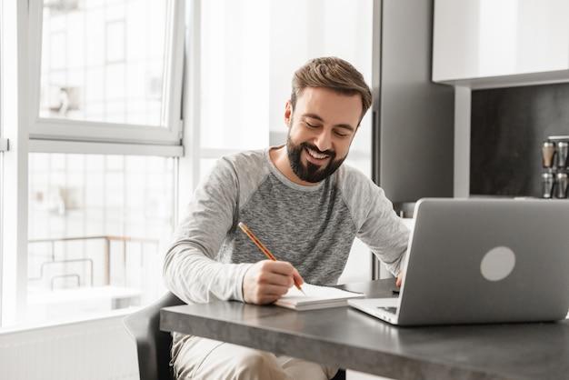 Ritratto di un giovane sorridente che lavora al computer portatile