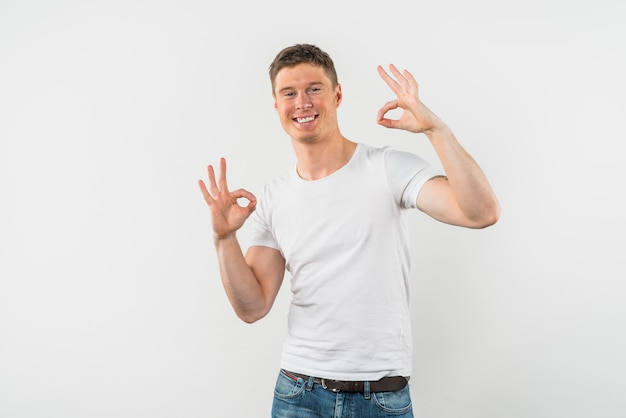 Ritratto di un giovane sorridente che mostra il segno giusto contro il contesto bianco