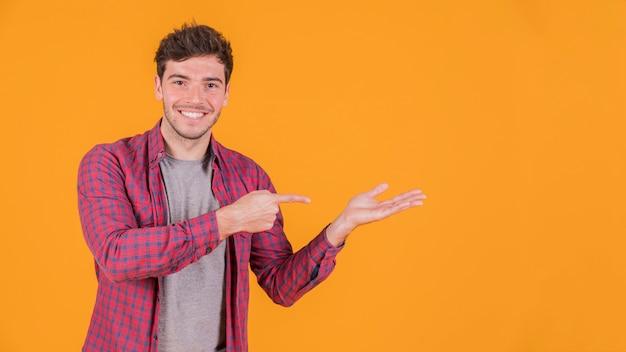 Ritratto di un giovane sorridente che punta a qualcosa contro sfondo colorato