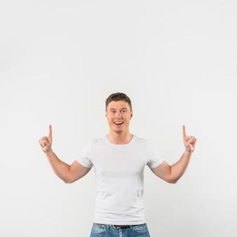 Ritratto di un giovane sorridente che punta le dita verso l'alto su sfondo bianco