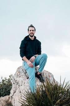Ritratto di un giovane sorridente che si siede sulla roccia che esamina macchina fotografica contro il cielo blu