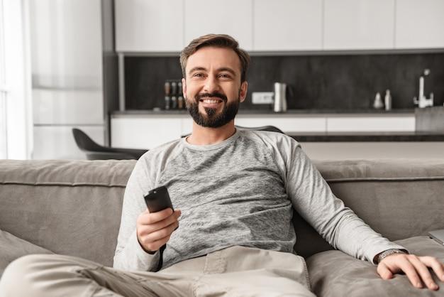 Ritratto di un giovane sorridente che tiene il telecomando della tv