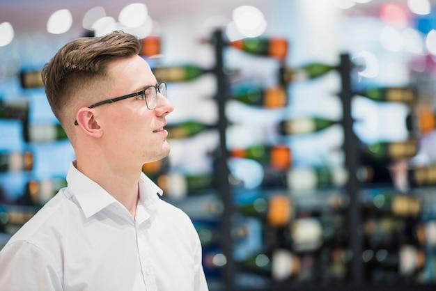 Ritratto di un giovane sorridente in piedi di fronte a bottiglie bar disposti