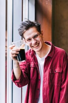 Ritratto di un giovane sorridente, mostrando il bicchiere di birra a porte chiuse