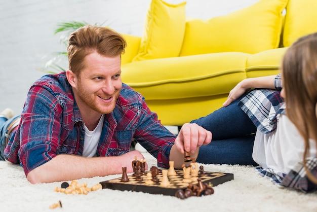 Ritratto di un giovane sorridente sdraiato sul tappeto a giocare a scacchi con la sua ragazza