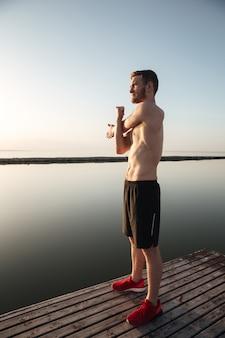 Ritratto di un giovane sportivo senza camicia riscaldando prima di fare jogging