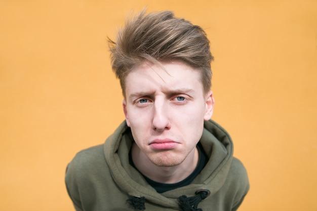 Ritratto di un giovane triste su una parete arancione. tirante divertente su una fine luminosa della parete in su