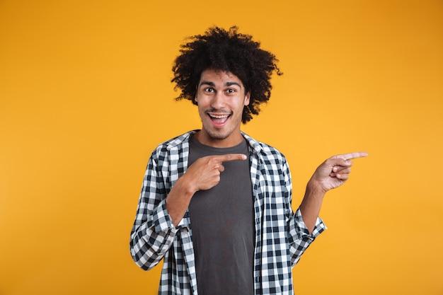 Ritratto di un giovane uomo africano allegro che punta le dita di distanza
