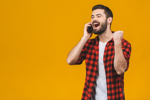 Ritratto di un giovane uomo allegro tenendo il telefono cellulare isolato su muro giallo, celebrando