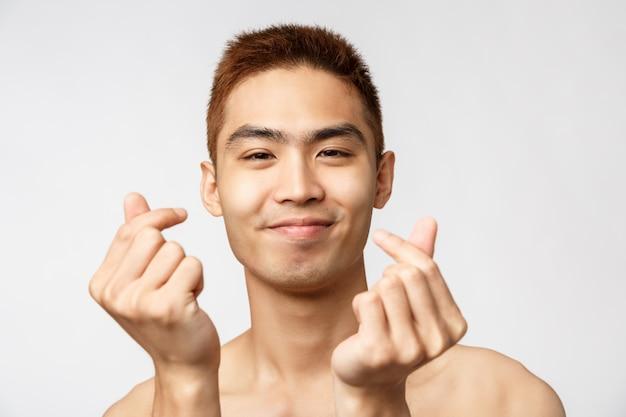Ritratto di un giovane uomo asiatico che mostra gesto