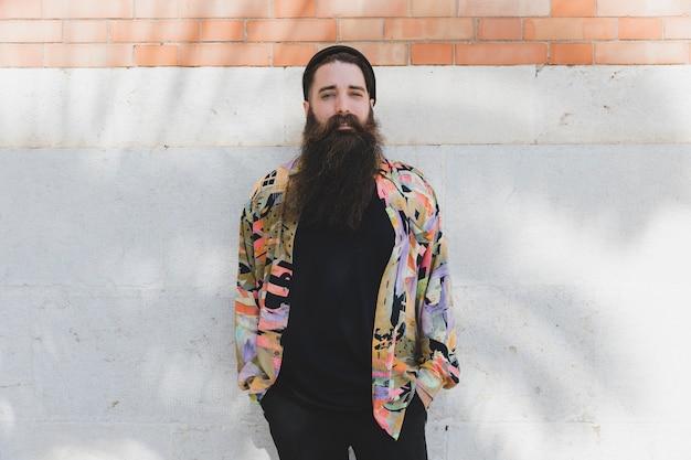 Ritratto di un giovane uomo barbuto in piedi contro il muro bianco