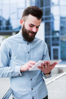 Ritratto di un giovane uomo bello utilizzando la tavoletta digitale