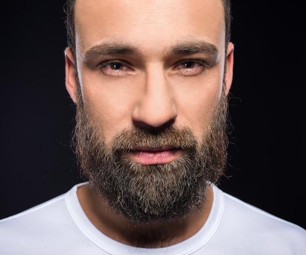 Ritratto di un giovane uomo brutale con la barba folta.