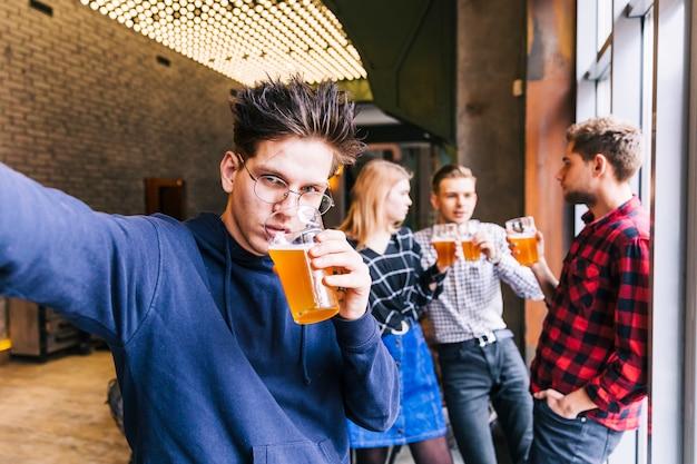 Ritratto di un giovane uomo che beve il bicchiere di birra prendendo selfie con i suoi amici in piedi a sfondo