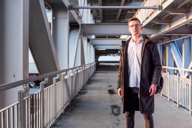 Ritratto di un giovane uomo che indossa giacca lunga in piedi sul ponte