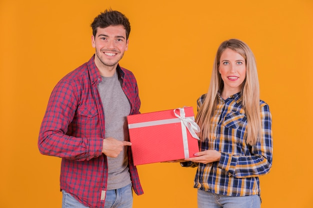 Ritratto di un giovane uomo che punta il dito sulla scatola regalo tenere dalla sua ragazza contro uno sfondo arancione