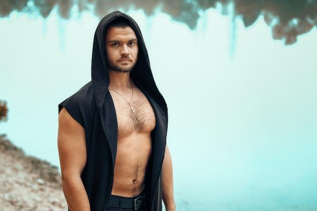 Ritratto di un giovane uomo che si leva in piedi con un torso nudo su una priorità bassa del lago.