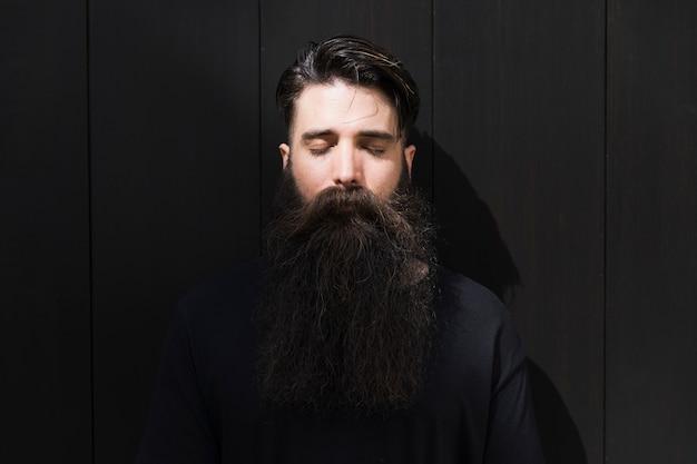 Ritratto di un giovane uomo con la barba lunga con gli occhi chiusi di fronte al muro di mattoni neri