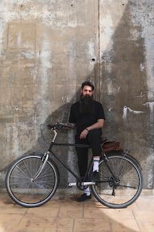 Ritratto di un giovane uomo con la sua bicicletta contro il muro di cemento stagionato