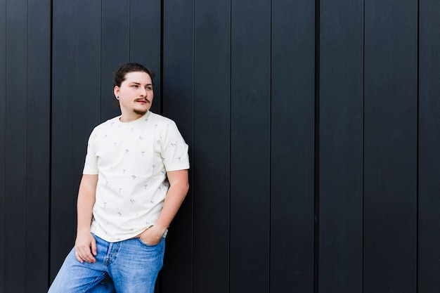 Ritratto di un giovane uomo con la sua mano nella sua tasca in piedi contro il muro nero