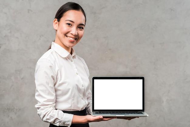 Ritratto di un giovane uomo d'affari asiatico sorridente che mostra computer portatile con la visualizzazione di schermo bianca