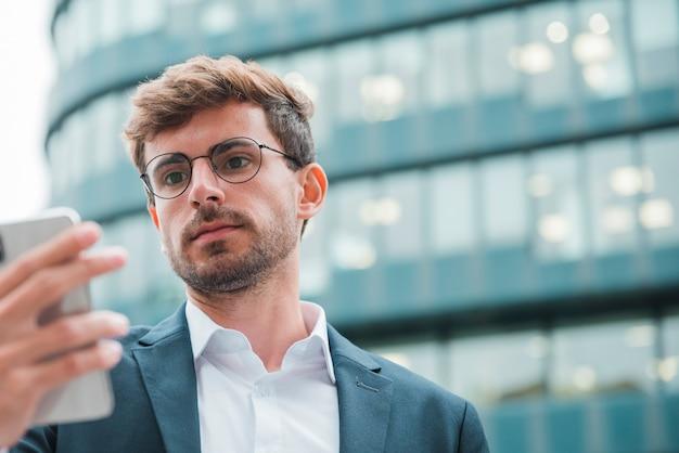 Ritratto di un giovane uomo d'affari che esamina il telefono cellulare che sta davanti alla costruzione corporativa