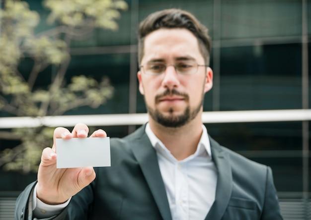 Ritratto di un giovane uomo d'affari che mostra biglietto da visita bianco in bianco