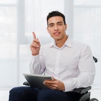 Ritratto di un giovane uomo d'affari che si siede sulla sedia a rotelle che tiene compressa digitale a disposizione che indica il suo dito verso l'alto