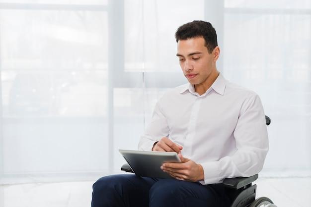 Ritratto di un giovane uomo d'affari che si siede sulla sedia a rotelle guardando tavoletta digitale