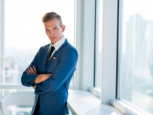 Ritratto di un giovane uomo d'affari con le braccia conserte