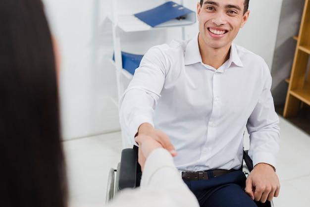 Ritratto di un giovane uomo d'affari disattivato sorridente che si siede sulla sedia a rotelle che stringe mano con la donna di affari
