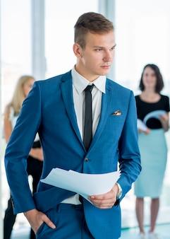 Ritratto di un giovane uomo d'affari in possesso di documenti in ufficio