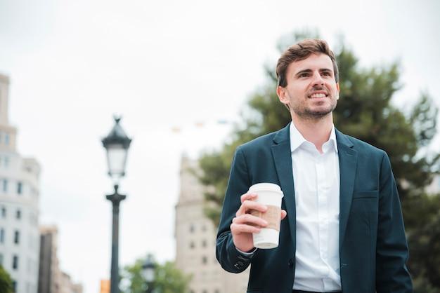 Ritratto di un giovane uomo d'affari sorridente che tiene la tazza di caffè asportabile a disposizione
