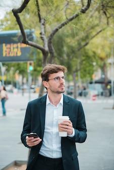Ritratto di un giovane uomo d'affari tenendo il telefono cellulare e tazza di caffè da asporto