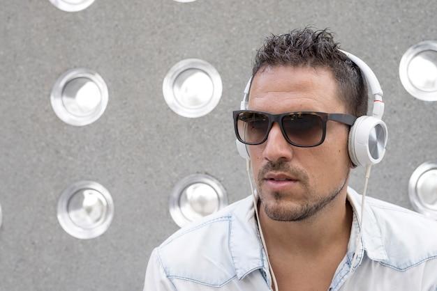 Ritratto di un giovane uomo di ascoltare musica con gli auricolari