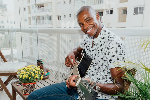 Ritratto di un giovane uomo felice seduto in balcone a suonare la chitarra guardando la fotocamera
