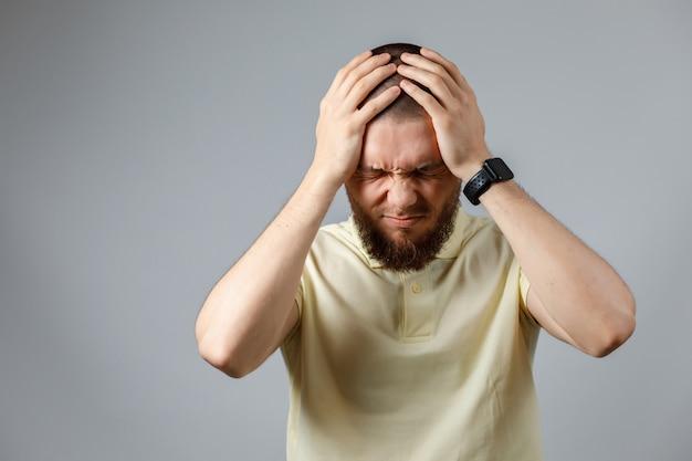 Ritratto di un giovane uomo sconvolto in una maglietta gialla che tiene la testa su grigio.
