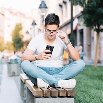 Ritratto di un giovane uomo seduto sulla panchina guardando lo schermo dello smartphone