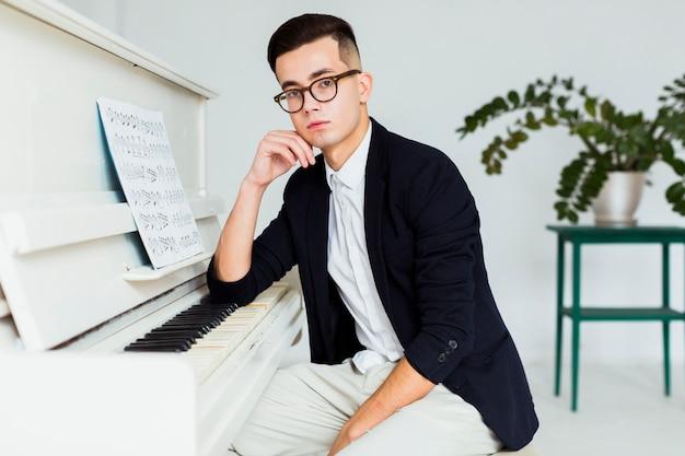 Ritratto di un giovane uomo seduto vicino al pianoforte guardando la fotocamera