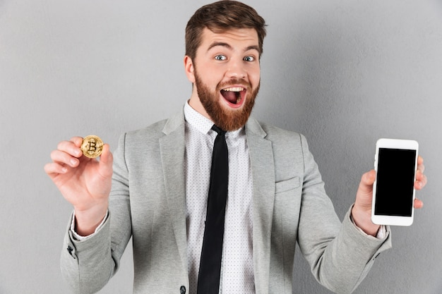 Ritratto di un imprenditore eccitato tenendo bitcoin