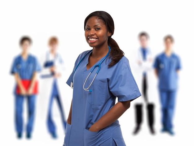 Ritratto di un'infermiera sorridente di fronte a un gruppo di medici