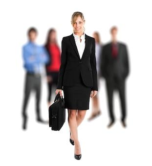 Ritratto di un manager femminile di fronte alla sua squadra a figura intera