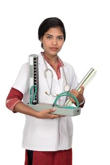 Ritratto di un medico della donna con lo strumento e lo stetoscopio di pressione sanguigna su spazio bianco.