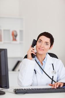 Ritratto di un medico femmina sorridente facendo una telefonata